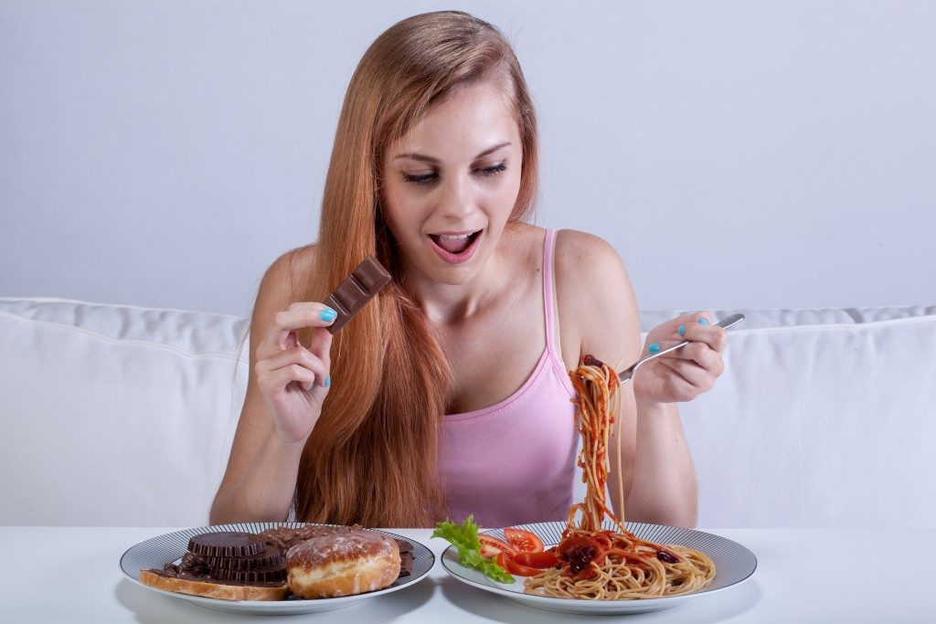 Girl suffering from bulimia eats dinner with dessert