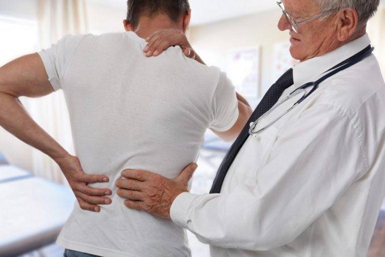 doctor examining a man with back pain