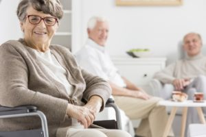 seniors sitting in a wheelchair and sofa smiling