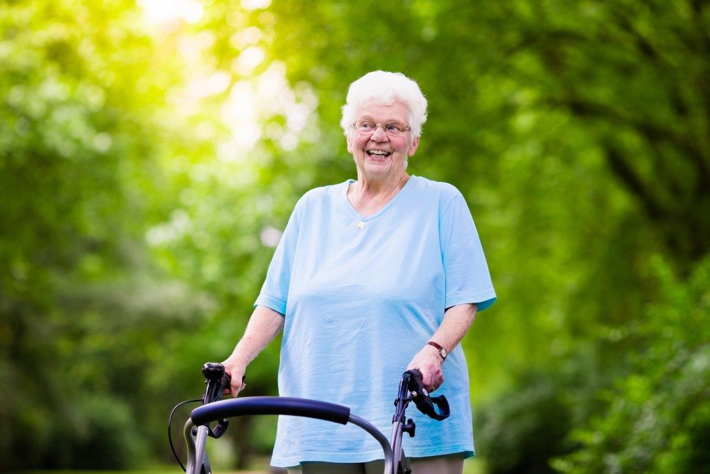 a senior lady smiling while holding on her walker