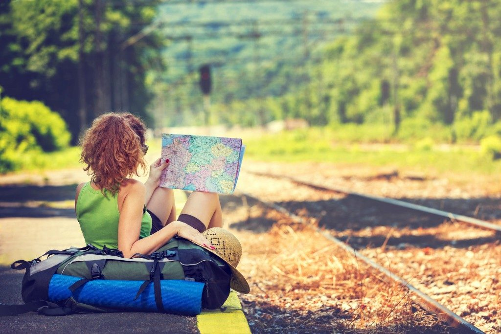Girl wearing backpack holding map