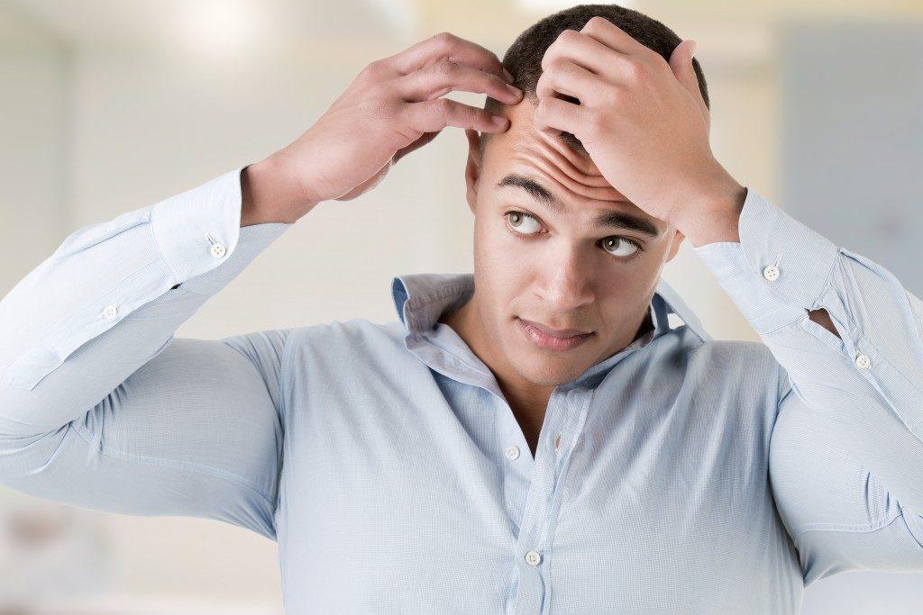 Man feeling his hair