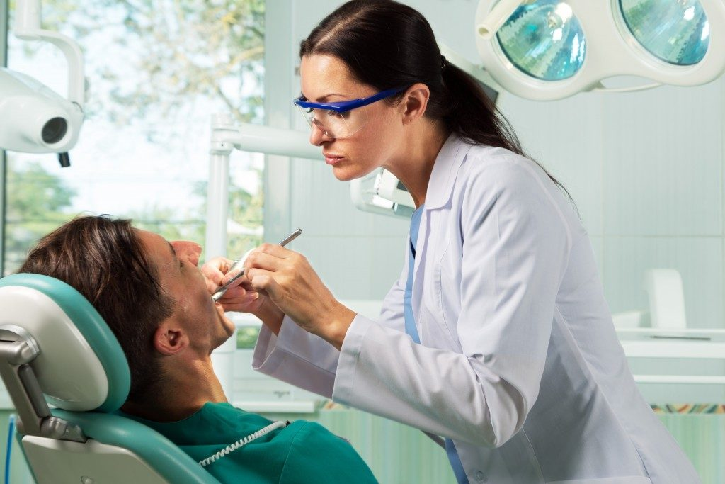 Dentist chekcking the patient's teeth