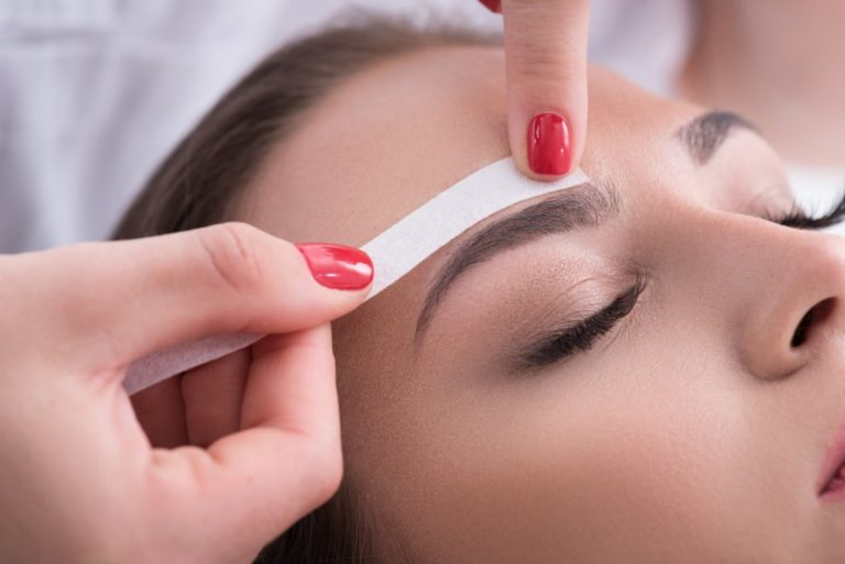 woman having her eyebrow trimmed