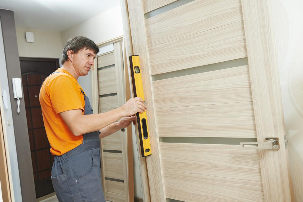 man leveling a door