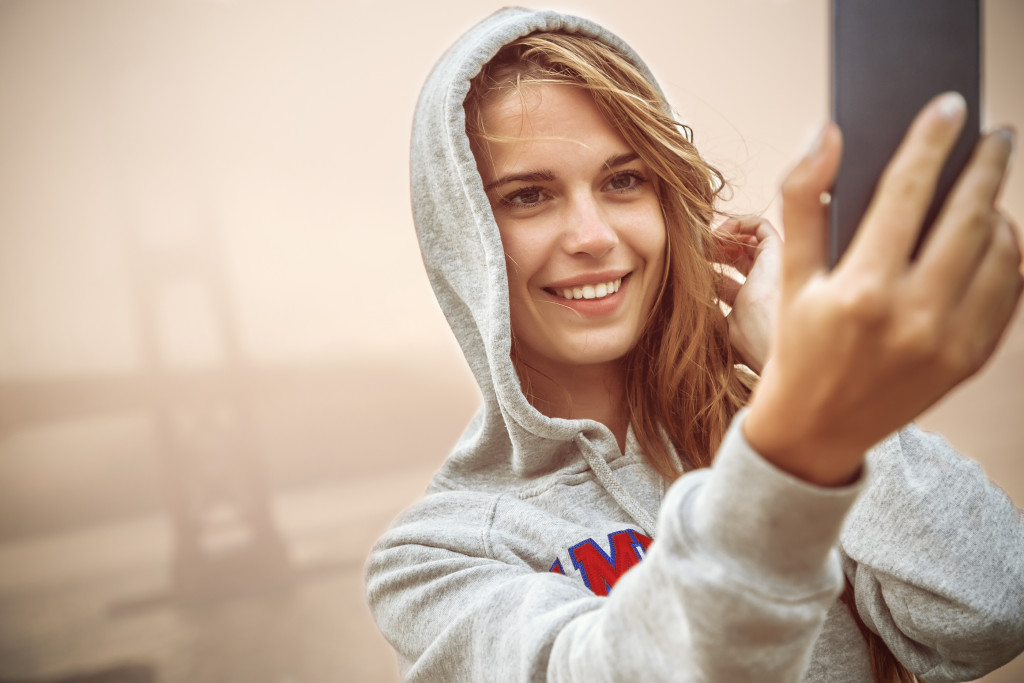 woman smiling while taking a picture of herself
